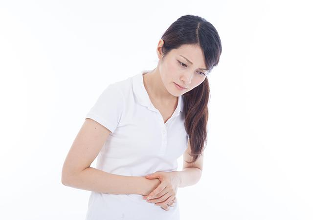胃痛に苦しむ女性のイメージ